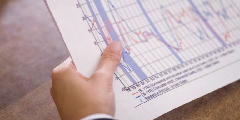 Hand holding paper showing economic indicators