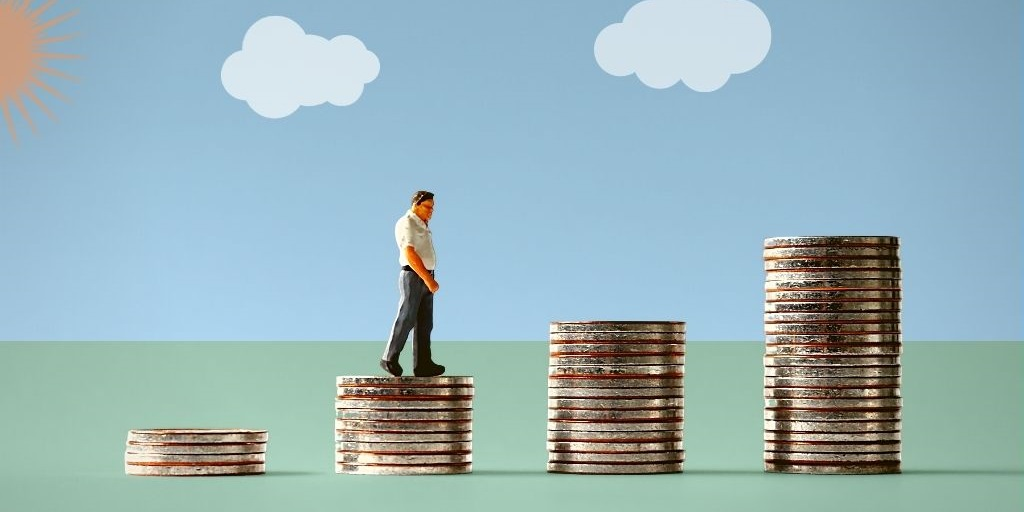 Man walking on stacks of coins