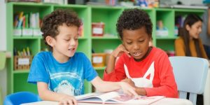 Two elementary students reading book in classroom